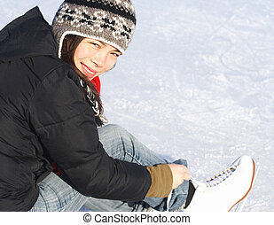 Ice skating. Young woman getting ready to ice skate outside...