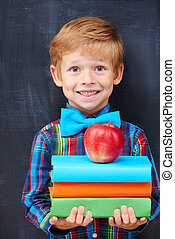 Smiling encoureged ginger boy holding a pile of books -...