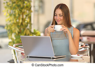 Relaxed woman watching a laptop in a restaurant and holding...