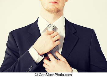 man adjusting his tie - close up of man adjusting his tie