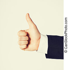 man showing thumbs up - close up of businessman hand showing...