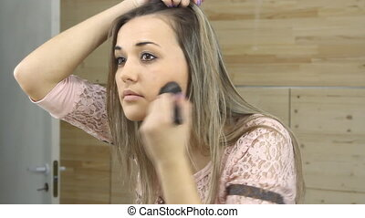 Beautiful girl looking in the mirror and applying cosmetic...