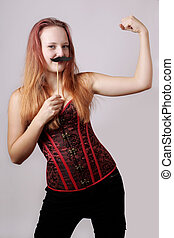 young woman with fake moustache on a stick showing off...