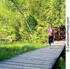 Woman Jogging on a Boardwalk in the Forest - A woman is...