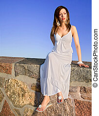 Beautiful Brunet Sitting on Top of a Stone Wall