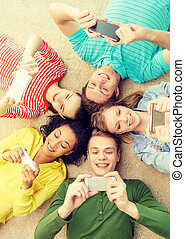 group of smiling people lying down on floor - education,...