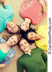 group of smiling people lying down on floor - education and...