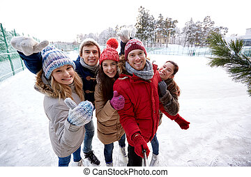 happy friends with smartphone on ice skating rink - people,...