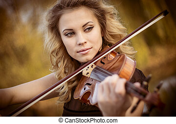 Musician - Young woman playing the violin at park Shallow...