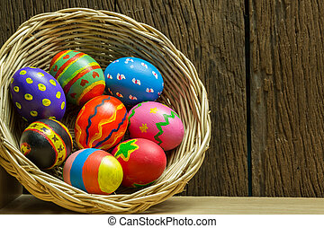 Easter eggs in basket and wood background