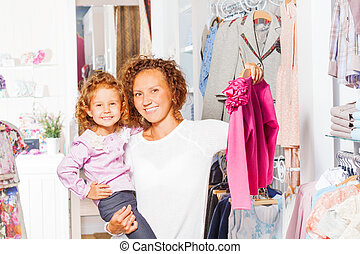 Smiling small girl with her mother shopping together in the...