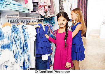 Two small girls shopping together and smiling - Two small...