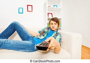 Boy switches remote control laying on white sofa alone at...