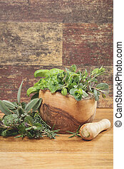 Different culinary herbs in a mortar over rustic table