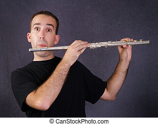 Man Playing Flute - A young man playing a metal flute which...