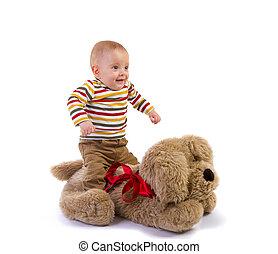 baby boy jump over plush dog on white background