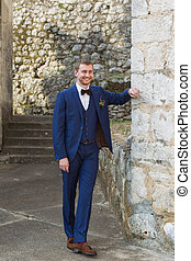 handsome groom in a blue suit smiling leaning on the wall