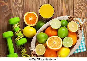 Citrus fruits in basket and dumbells. Oranges, limes and...