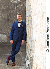 handsome groom in a blue suit leaning on the wall