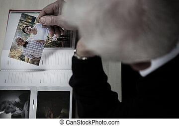 Windowed man watching photo album