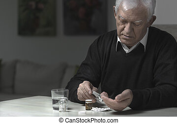 Man taking medicaments - Old aged and sad man taking...