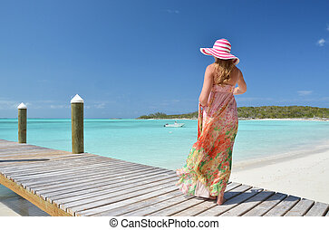 Girl at the wooden jetty looking to the ocean. Exuma,...