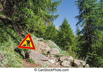 Road work sign on a path ascending into a forest.