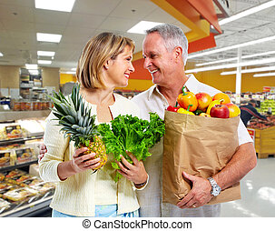 Elderly couple with vegetables. - Senior shopping couple...