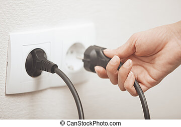 Electric plug - Woman pluging cable to the electric outlet