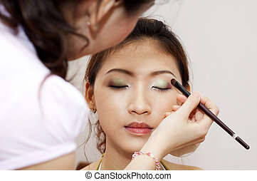Applying makeup - Woman applying cosmetic with applicator...