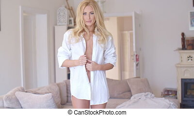 Sexy blond woman unbuttoning her shirt in a tantalizing...