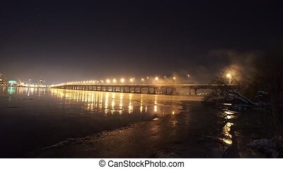 The river with illuminated bridge in winter night - The...