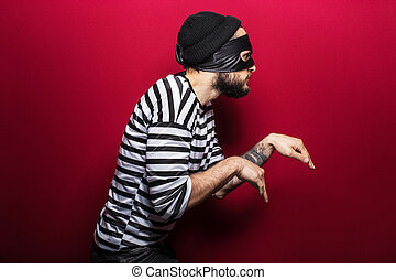 criminal, thief, robber, crime - A thief with mask slinking...