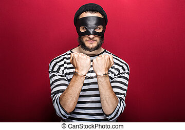 criminal, thief, robber, crime - Angry thief with handcuffs...