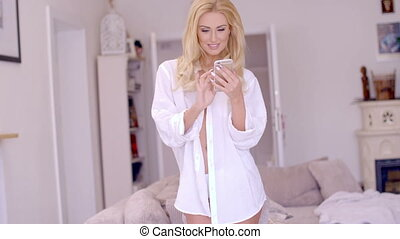 Attractive blond woman reading an sms or text message on her...