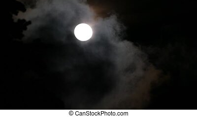 Moon in the night sky over running clouds