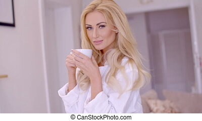 Alluring Blond Woman with Coffee Looking at Camera - Close...