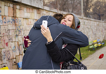 Boy hugging a girl while she looks at her smartphone...