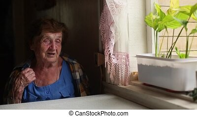 Old lonely woman sitting near the window in his house. (HD)...