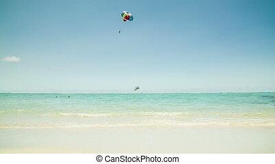 Parasailer at beach in Mauritius - Parasailing offers you a...