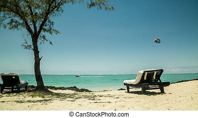 sunchair at beach in mauritius with parasailer - relaxing at...