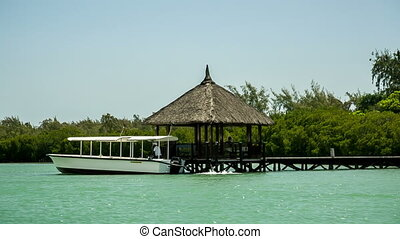 old wooden pier in mauritius with passenger boat leaving