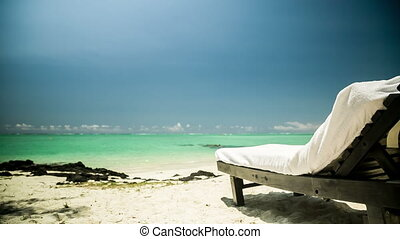 Man relaxing in sun chair at beach - young man relaxing on a...