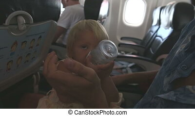 child drinks water sits on fathers knees in air