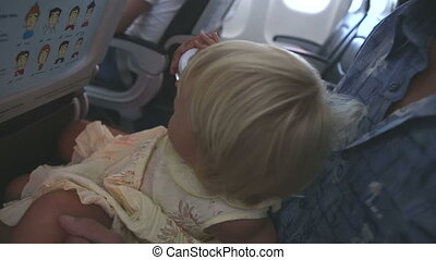 child sits on fathers knees and play in airplane - small...