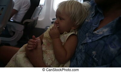 child sits and eats on fathers knees in airplane - small...