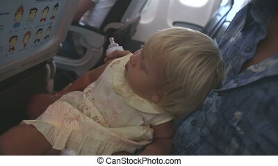 child sits on father's knees and play in airplane - small...