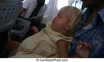 child sits and misbehaves on fathers knees in airplane -...