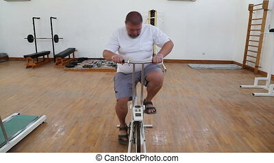 overweight man exercising on bike simulator