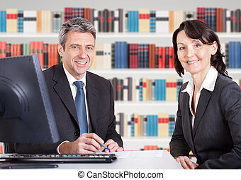 Two Businesspeople Sitting At Office Desk - Two Happy Mature...